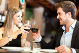 Couple in a romantic dinner toasting with wine