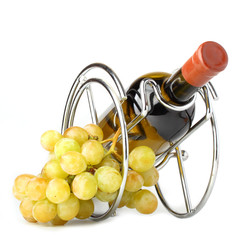 white wine bottle in metallic support and grapes