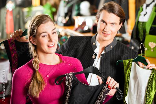 Junges Paar kauft Tracht oder Dirndl in einer Boutique