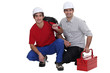Two electricians crouching down