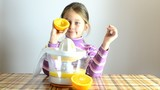 girl making fresh orange juice by juicer