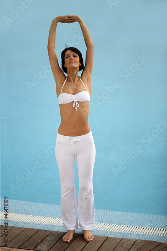 Woman stretching at a poolside