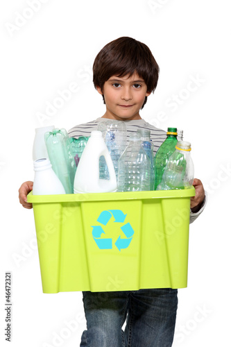 kid holding recycling tub full of empty plastic bottles