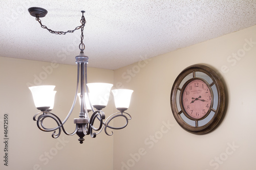 Old ceiling lamp and old clock in a new house