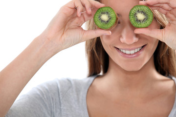 Woman covering her eyes with slices of kiwi