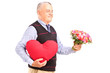 A gentleman holding a red heart and flowers
