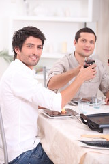 Men clinking their glasses at table