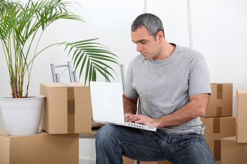 man amid removal boxes working on laptop