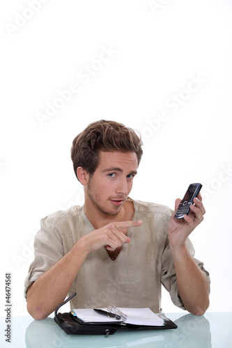 Man with a ringbound agenda pointing at a cellphone