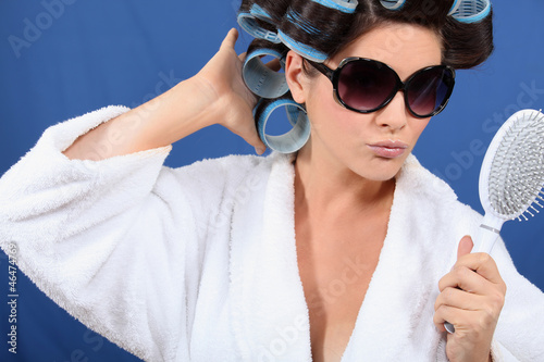 Woman with hair in rollers holding a brush and sunglasses