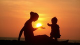 Silhouette of carefree mother and daughter over sunset
