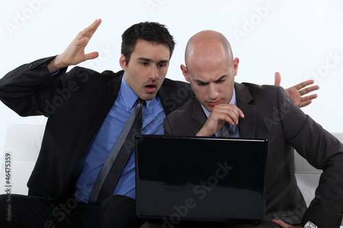Two stressed office worker with laptop