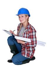 Tradeswoman writing on a clipboard