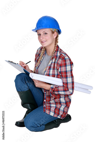 Tradeswoman writing on a clipboard