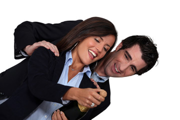 Business couple celebrating with bottle of champagne