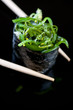Vertical shot of chopsticks holding sushi with chuka salad