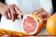 Senior woman slicing a grapefruit, horizontal shot