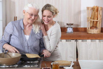 A lady and her daughter cooking crepes.