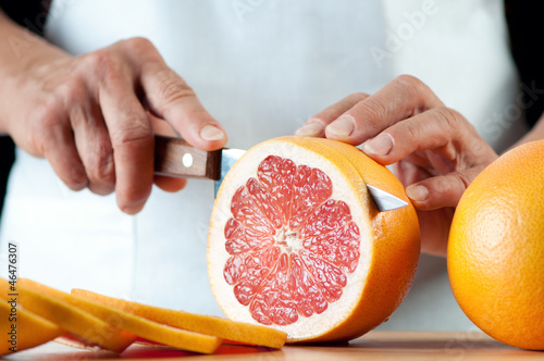 Senior woman slicing a grapefruit, horizontal shot