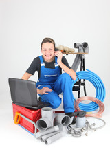 Female plumber knelt down by equipment