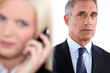 Man looking on as a woman takes a phone call