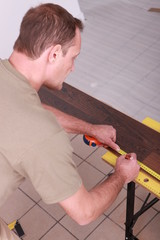 Man marking off laminate flooring with pencil