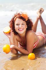 The beautiful girl with orange on the sea