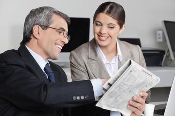 Geschäftsmann zeigt Kollegin Zeitungsmeldung