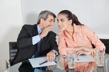Manager flüstert Geschäftsfrau ins Ohr