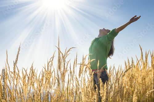 Happy young girl raising her arms with bliss and joy