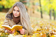 Pretty young woman reading in a park in autumn