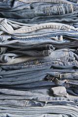 Montón de pantalones vaqueros ordenados en un estante