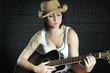 Frau mit Gitarre vor grauer Wand