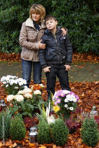 Mutter und Kind stehen an einem Grab