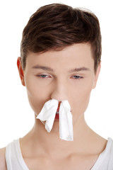 Sick man with a cold with tissue in his nose