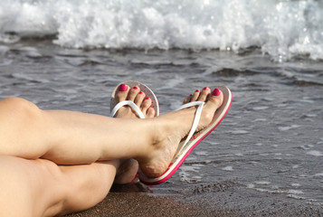 Woman Feet with flip flops on the Beach