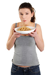 Young beautiful woman eating spaghetti
