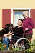 Seniorin schiebt junge Frau mit Hund durch den Park