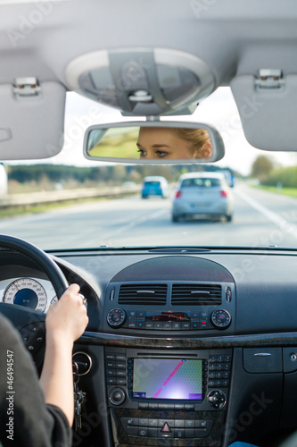 Young woman driving by car on motorway