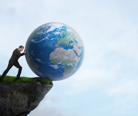 Businessman pushing planet Earth off the cliff