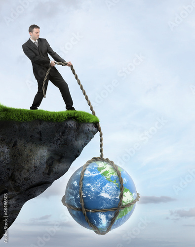 Businessman saving Earth from falling of the cliff