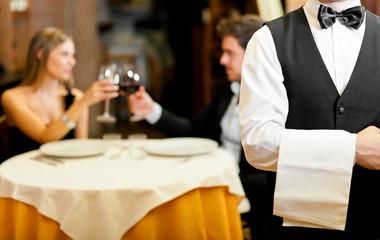 Couple at restaurant: focus on waiter