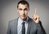 Young businessman criticizing on gray background poster