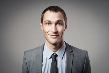 Cool businessman portrait on grey background