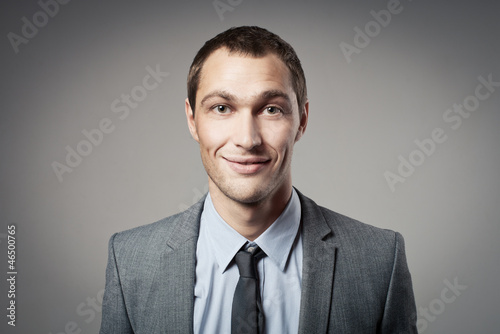 Cool businessman portrait on grey background