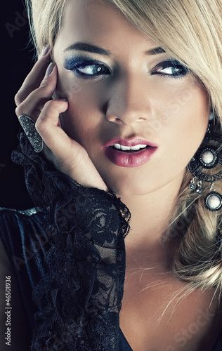 Close up portrait of a blond woman on black background