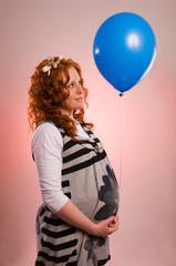 Beautiful pregnant woman holding balloon