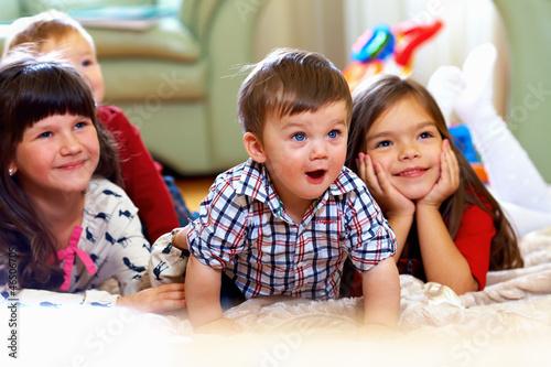 Leinwanddruck Bild group of happy kids watching tv at home
