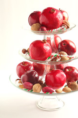 Apples, pomegranates, nuts and candy canes in a vase
