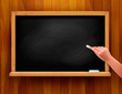 Blackboard with hand on wooden background